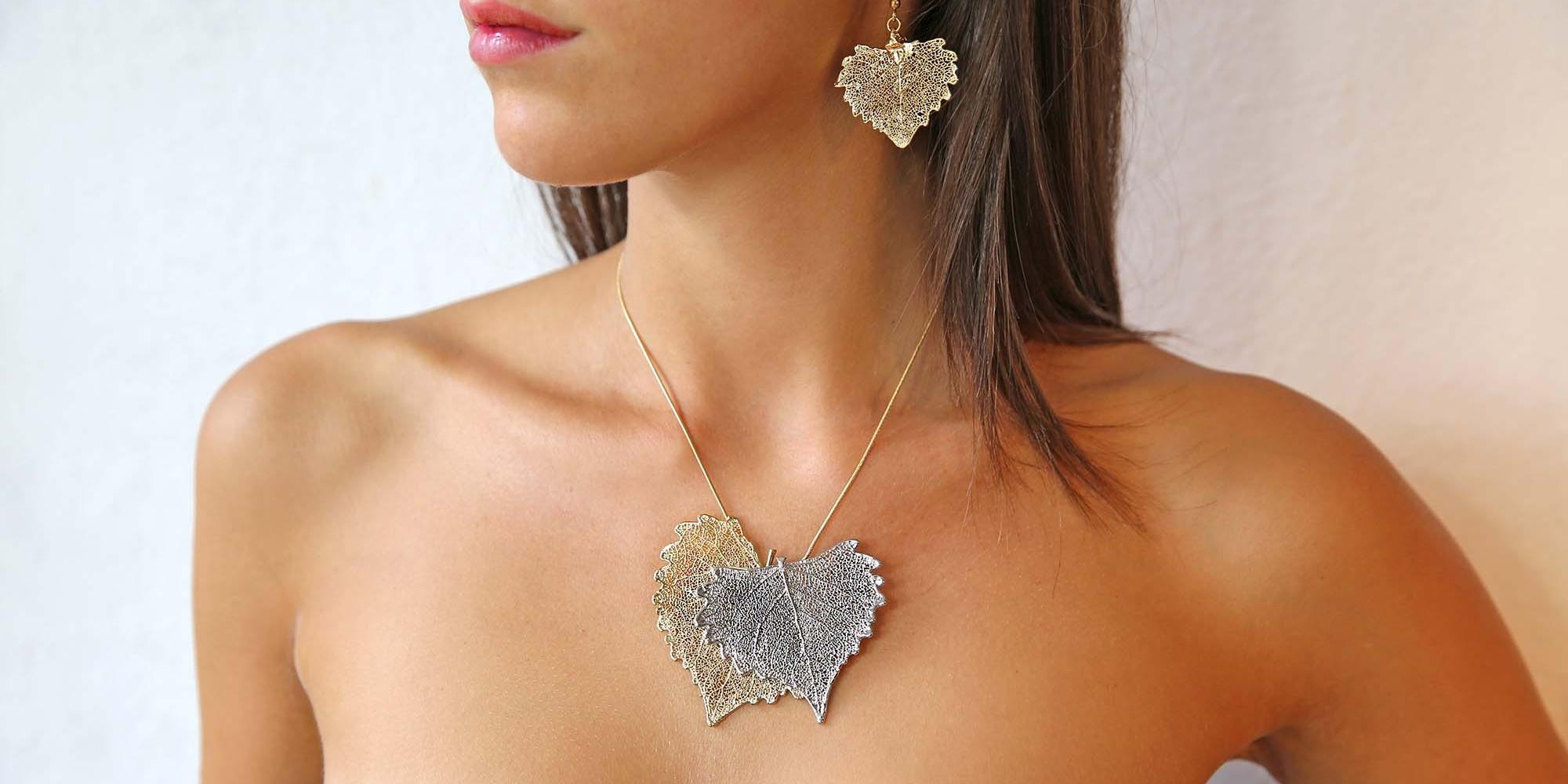 Parure indossata da modella di orecchini di vere foglie di cotone placcate argento e ciondolo due toni con due foglie di cotone una placcata oro e l'altra argento