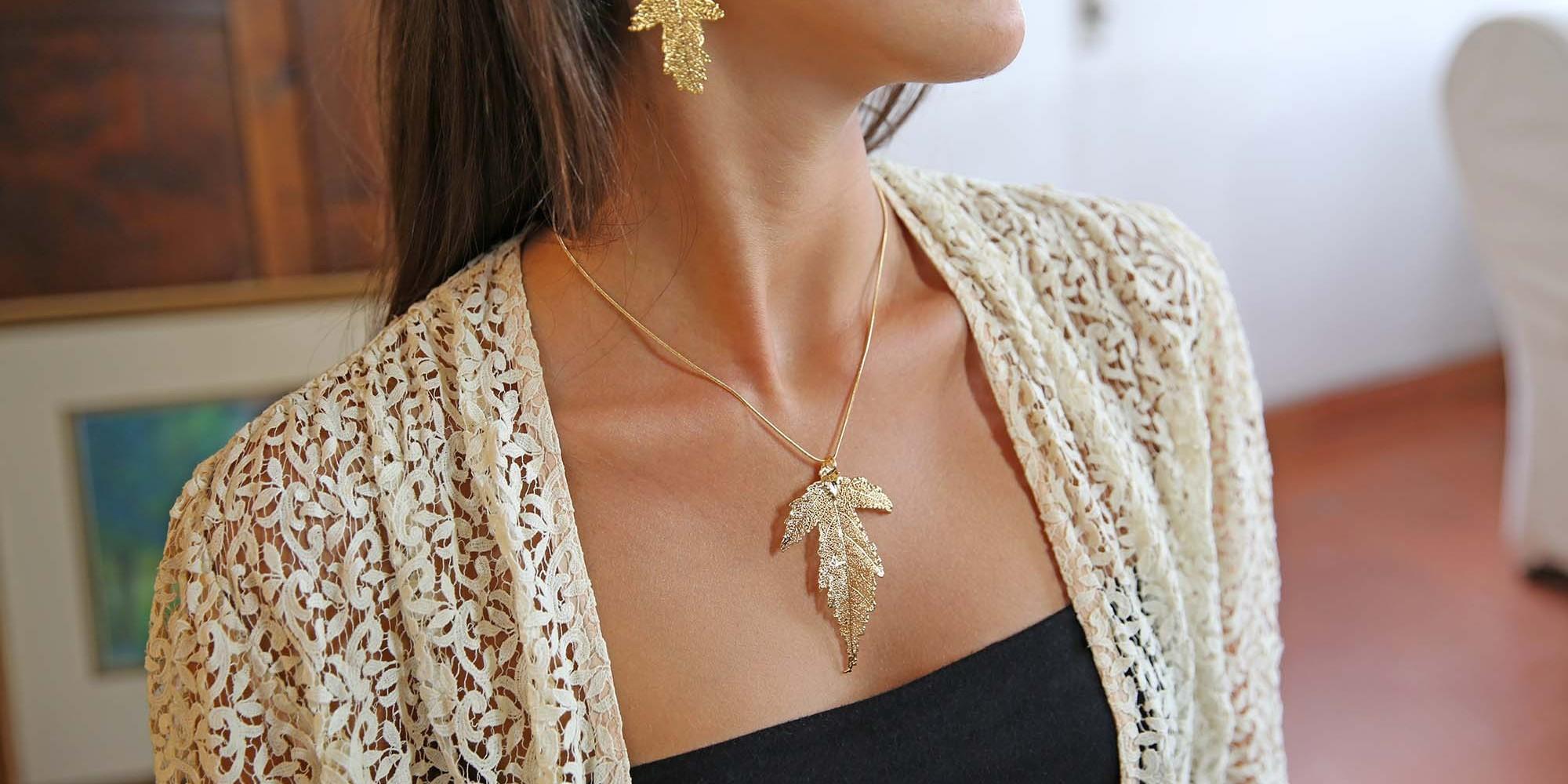 Parure indossata da modella con orecchini e ciondolo di vere foglie di gelso placcate oro