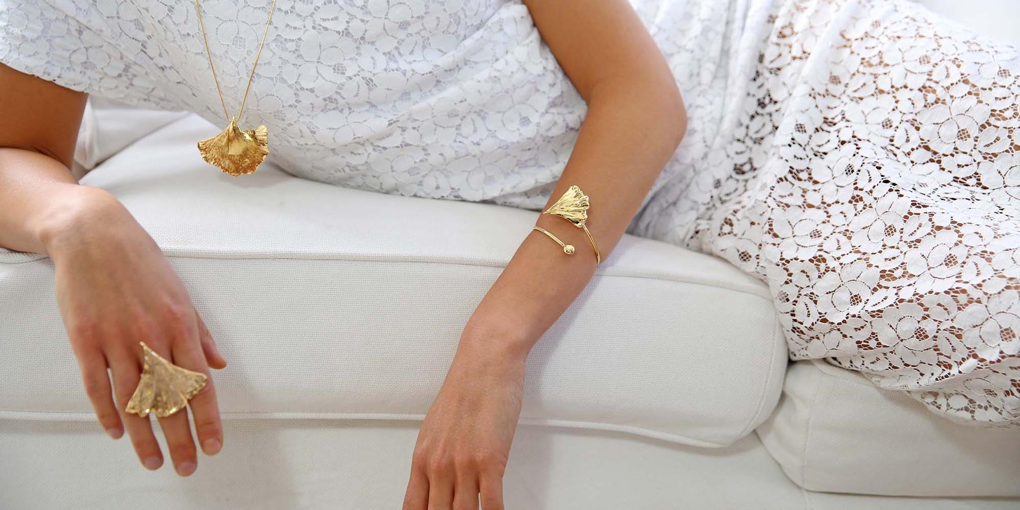 Parure indossata da modella con ciondolo, anello e bracciale di vere foglie di ginkgo biloba placcate oro