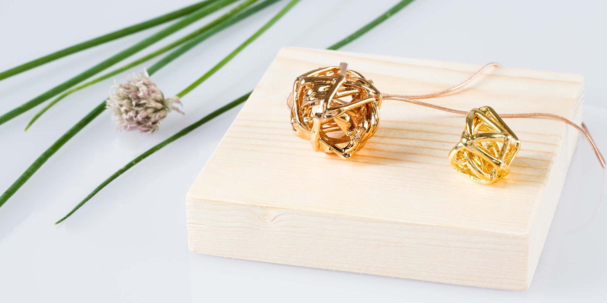Due ciondoli con veri giunchi legati a formare sfere irregolari placcati uno oro rosa e uno oro