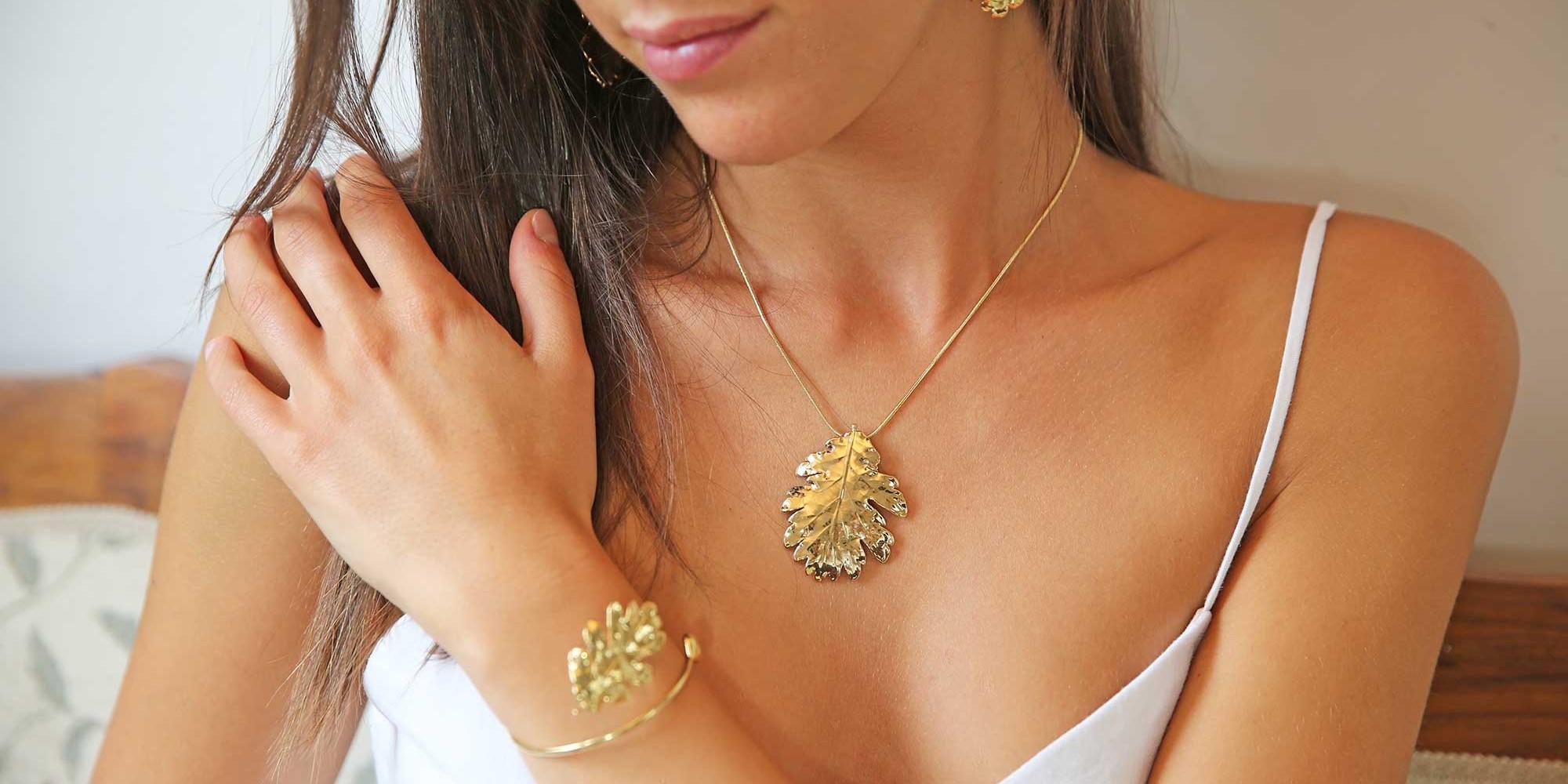 Parure indossata da modella con orecchini, ciondolo e bracciale di vere foglie di quercia placcate oro
