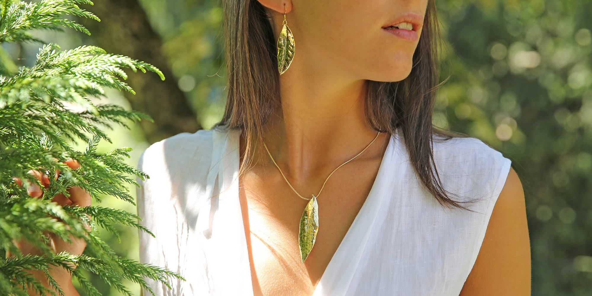 Parure indossata da modella con ciondolo e orecchini di vere foglie di ulivo placcate oro
